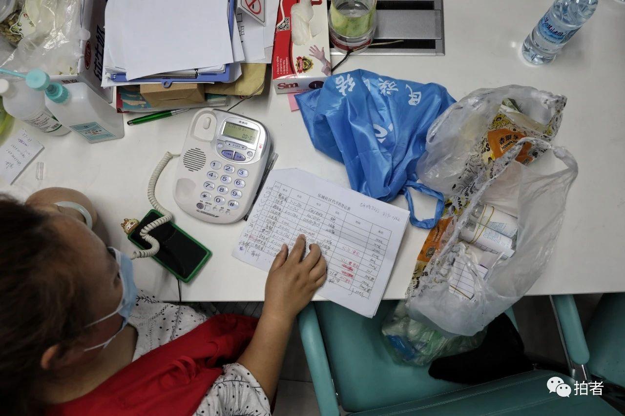 △6月20日,社区服务站内,王志平打电话告诉居民来取药。