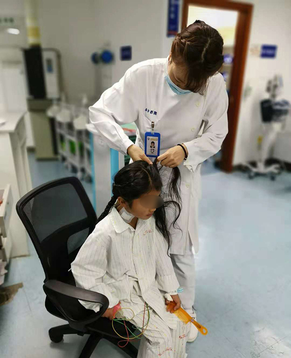 医护人员给患儿莫朗姐编辫子。 本文图片均为东方医院 供图