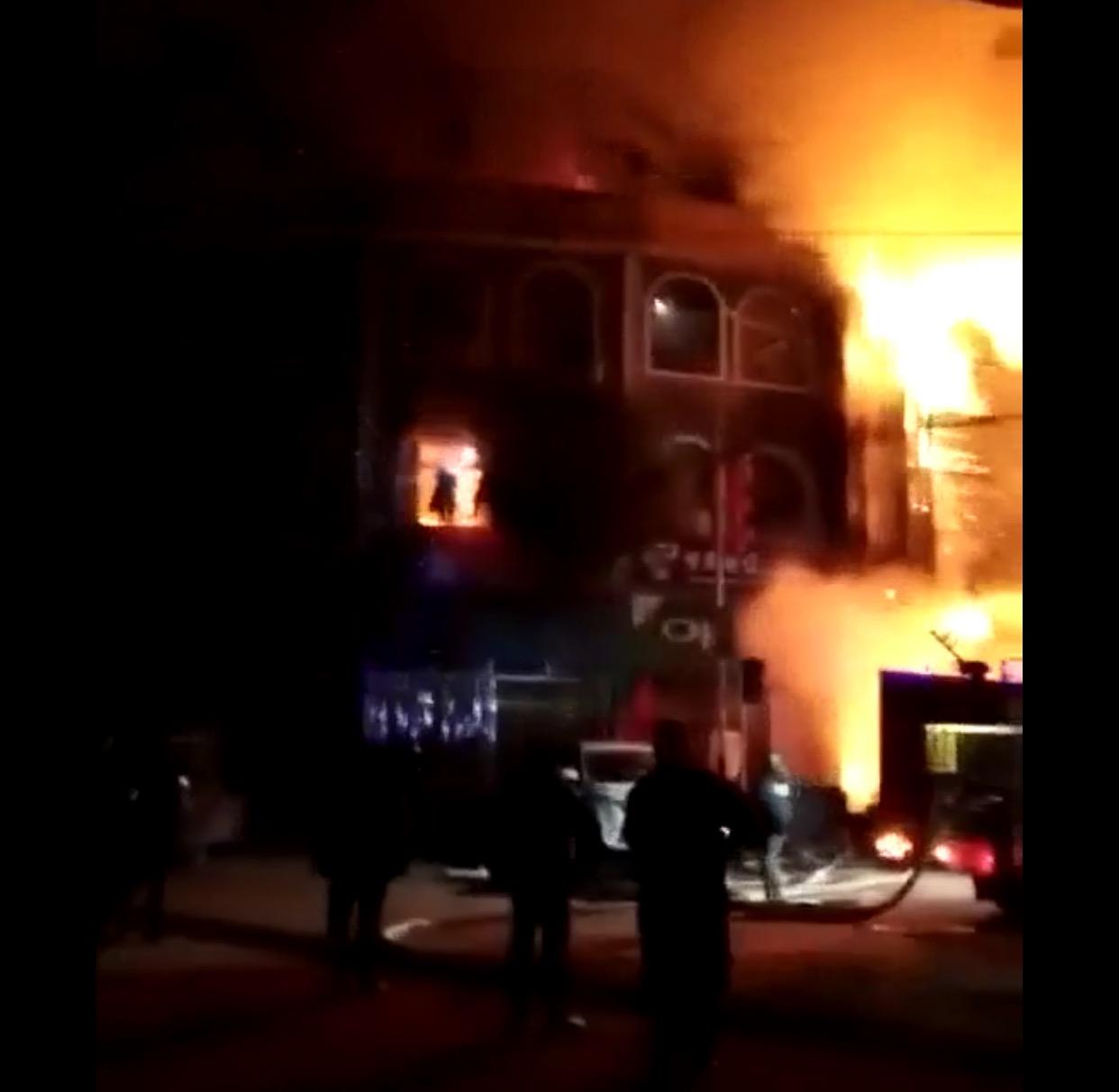 现场火势恶猛,现在击者称有人经过窗户爬下逃生。受访者供图