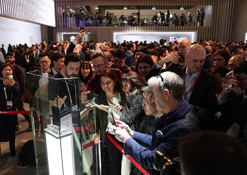 今年2月在巴塞罗那举行的2019年世界移动通信大会上,华为发布的首款5G手机引发参观者围观。(美联社资料图片)