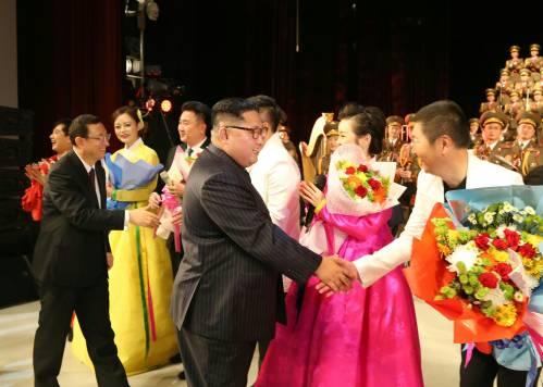 11月3日,朝鲜劳动党委员长、国务委员会委员长金正恩(中)在平壤观看中朝文艺工作者首场联合演出后上台同主要演员一一握手。 (新华社)