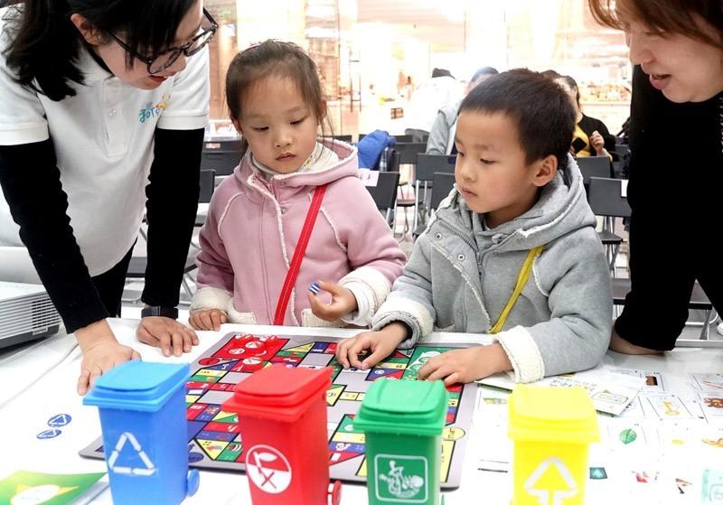 """△2019年3月24日,上海市静安区的志愿者和辖区内的部分市民开展垃圾分类""""乐回收""""公益活动,不少小朋友参与其中,学习了解环保知识。"""