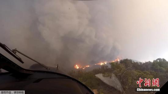 资料图:近日,在加州伍尔西山火火灾期间,救援人员动用直升机进行救援工作,飞行员所使用的头盔相机记录下了现场画面。图为直升机完成救援后离开火灾现场。