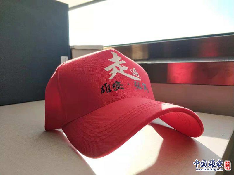 """印有""""走遍雄安·张岗""""字样的幼红帽。中国雄安官网演习生李鑫摄"""