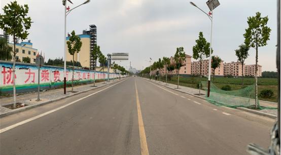 北金集团及旗下公司厂区大多布局在北金村社区周围。图右侧即是社区,左侧是北金集团旗下水泥厂。环球网记者现场大致测量,该街道宽约15.6米。