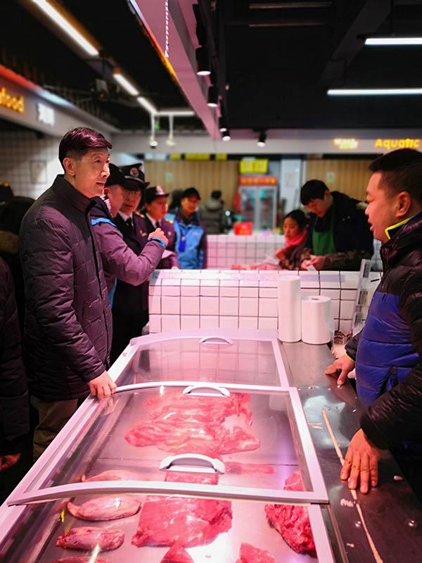 陈学军检查菜场肉成品。 上海市市场监督管理局供图