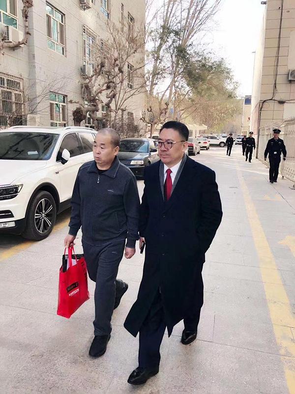 李建功和申诉代理人王誓华走出法庭。 受访者 供图