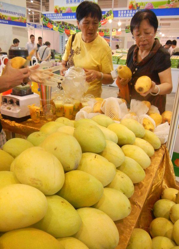 2014年,两名大陆居民在海峡两岸农牧渔产业交易会上选购台湾水果。 新华社资料图
