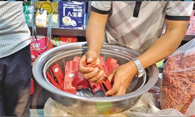 """8月18日,宁夏中卫市鼓楼东街一枸杞专卖店,老板正在往有""""中宁""""字样的包装袋里装枸杞,但这些枸杞并不是产自中宁。"""