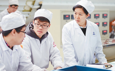 赵鸿飞(右一)与同事讨论工作细节。  资料照片