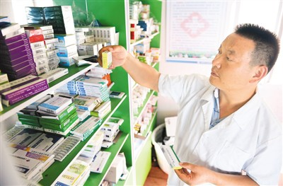 安徽省六安市金寨县响洪甸水库的村医余家军在卫生站为村民取药。新华社记者 刘军喜摄