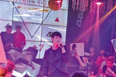 """范一贤在酒吧开唱,背景屏幕显示了其""""代表作""""。"""