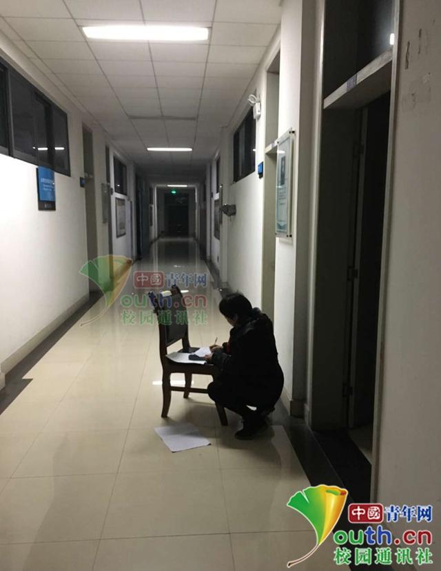 冉春芳在走廊借光蹲着批阅试卷。 本文图片 中国青年网