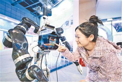 觀眾在中關村論壇現場與自適應機器人互動。本報記者 賀 勇攝