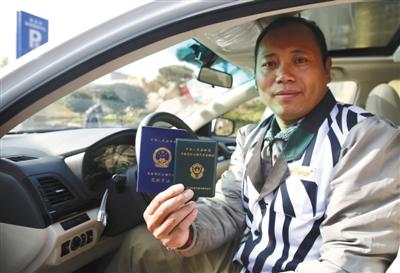 11月9日,山东泰安,一位网约车司机展现手中的网约车从业资格证。 图/视觉中国