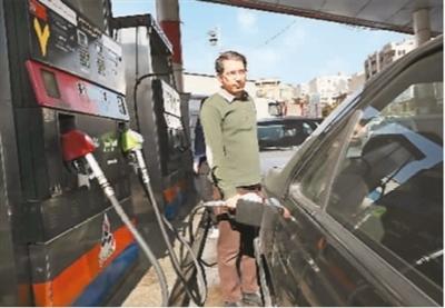 图为近日在伊朗德黑兰,一名男子给汽车加油。伊朗政府11月15日宣布上调汽油价格并实施新的配给制度。   新华社/美联