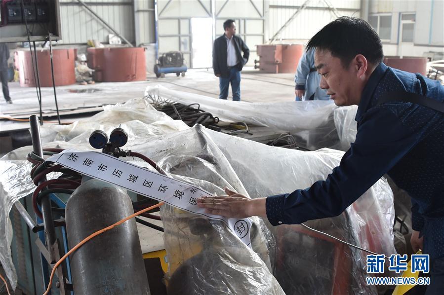 4月17日,一名济南市环保局的工作人员在查封设备 图片来源:新华社
