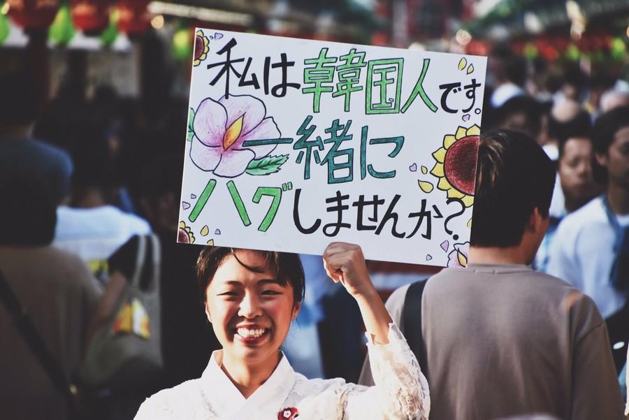 """尹秀荣手举的牌子上写着""""我是韩国人,可以给我一个拥抱吗""""(BuzzJapan)"""