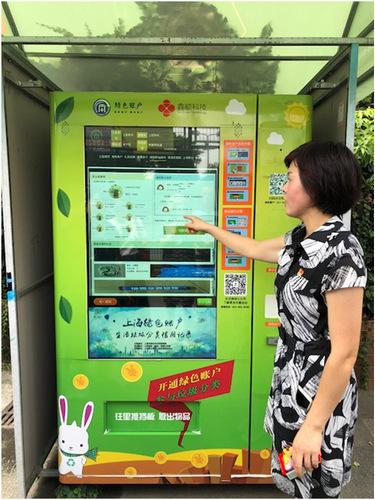 社区干部解说绿色账户自动积分兑换机的使用方法 田 泓 摄