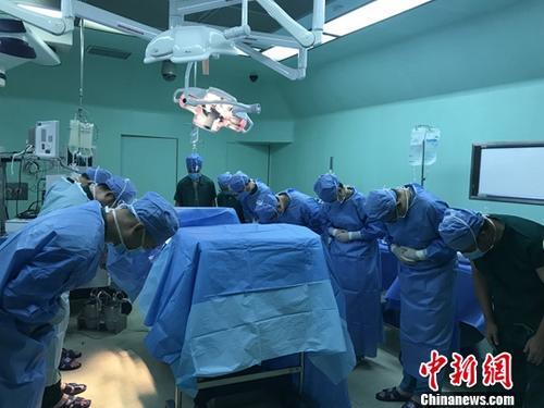 原料图:大夫向施舍器官的逝者鞠躬。中新社发 胡琼珍 摄