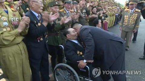 今年7月,金正恩俯身与参添老兵大会的金铁万交谈。(韩联社)