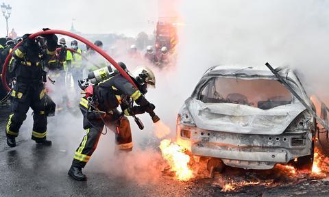 示威者焚烧汽车(来源:英国卫报网)