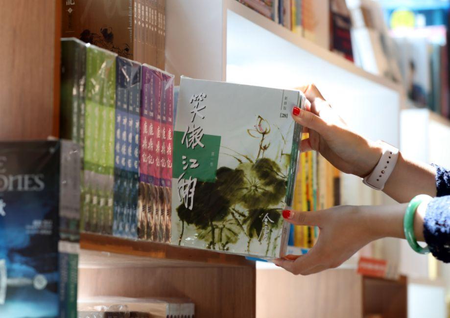 10月31日,在香港的一家书店,别名读者从书架上掏出金庸作品。新华社记者李钢摄