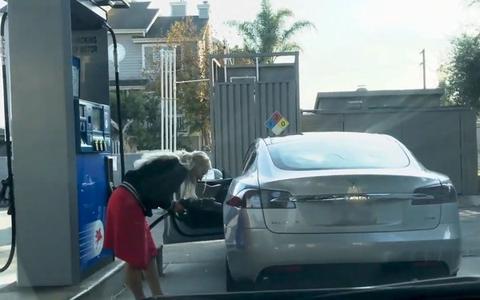 女司机将添油枪放入充电孔中 (图源:视频截图)