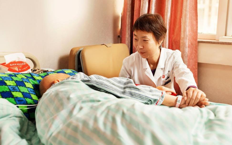 北京海医院安宁疗护病房主任秦苑在看望一位患者。受访者供图