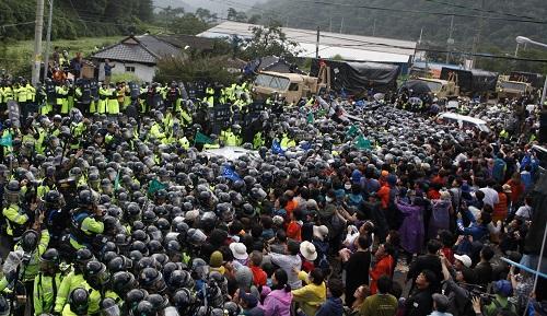 """2017年9月7日,在韩国庆尚北道星州郡,韩国民众在""""萨德""""部署地附近与警方发生冲突,民众彻夜阻拦""""萨德""""装备进入部署地。新华社记者姚琪琳摄"""