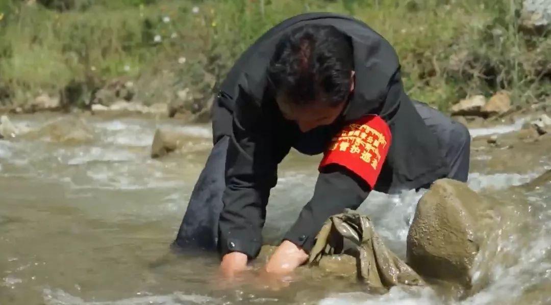 """▲戴着""""生态管护巡查""""袖标的当地居民正在清理河道垃圾。(报道截图)"""