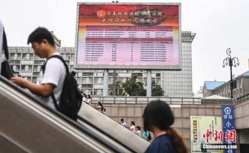 资料图:2017年8月23日,济南火车站广场大屏幕24小时循环播放失信被执行人信息,引得许多旅客驻足观看。 中新社记者 张勇 摄