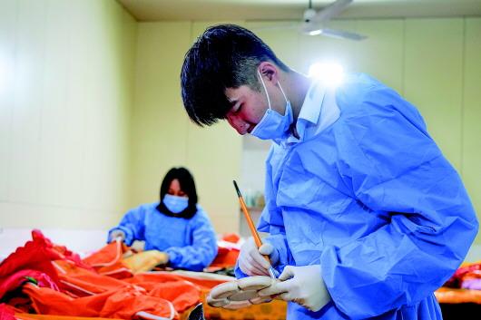 王旭正在殡仪馆整容室给逝者整理仪容。来源:新华每日电讯
