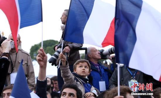 图为马克龙的声援者在祝贺胜选的集会上挥旗。中新社记者 龙剑武 摄