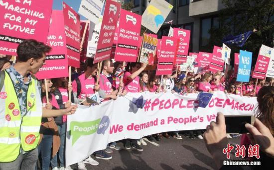 """2018年10月20日,67万英国民众汇集在伦敦议会广场举办示威游行勾当,呐喊对于英国脱欧终极协定举办全夷易近投票。图为示威游行队伍拉着横幅、举着标语牌,呐喊""""人夷易近投票""""。中新社记者 张平 摄"""