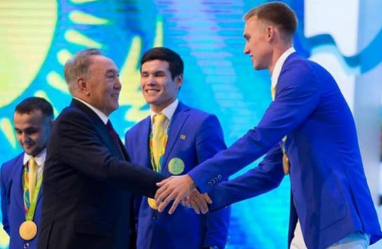 纳扎尔巴耶夫与游泳选手巴兰丁握手