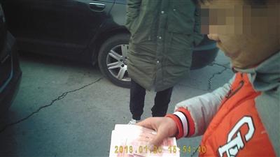 丰台一检测场,一名车虫正在收代验车的费用。新京报记者 顾开贵 摄
