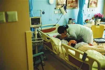 北京大学首钢医院安宁疗护中心,因为老人耳背,医护人员需要趴在老人耳边才能和老人交流。摄影/新京报记者 彭子洋