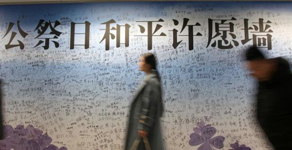2017年12月11日,江苏省南京市,人们从侵华日军南京大屠杀遇难同胞纪念馆旁云锦路地铁站的国家公祭和平许愿签名墙前走过。 东方IC 图