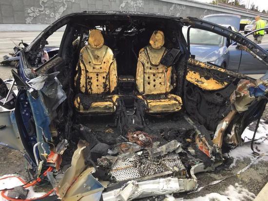 一辆Model X发生碰撞后起火烧毁,车底电池板露出。图/Dean C。 Smith